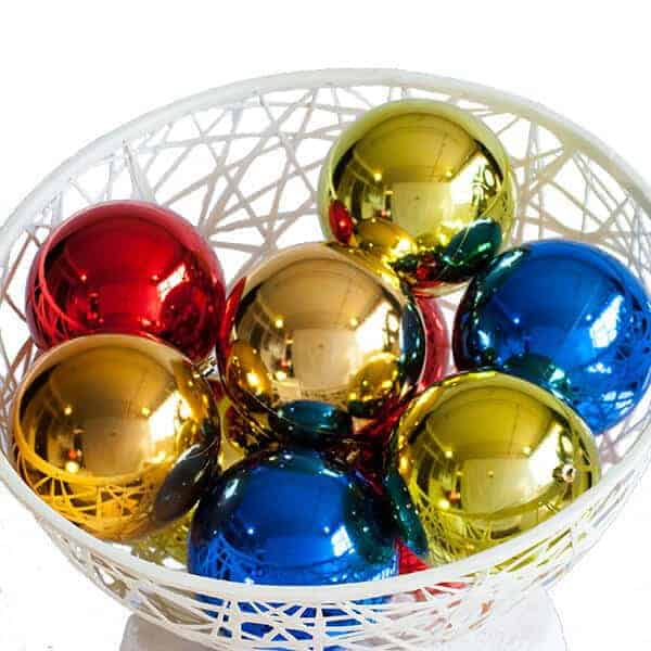 White basket filled with various coloured shiny christmas baubles