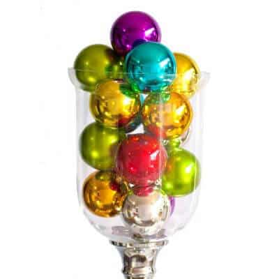 Glass vase filled with various coloured UV baubles