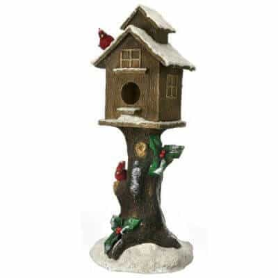 Snowy birdhouse on tree stump prop