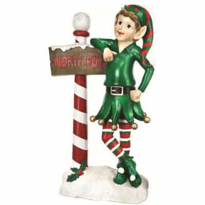 Elf leaning on snowy North Pole sign