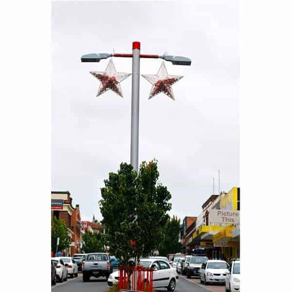 Two Masson stars hanging from street pole, filled with red baubles